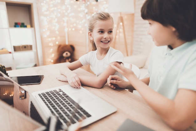 Intelligente kinder machen hausaufgaben mit laptop boy hilft mädchen. Premium Fotos