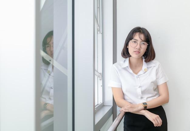 Intelligente studentinnen in der uniform stehen nahe fenster Premium Fotos