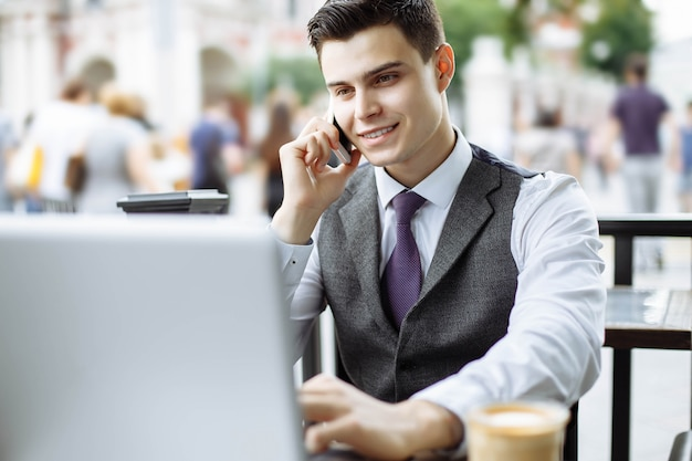 Intelligenter manager, der kaffeepause hat und am telefon im café spricht Premium Fotos