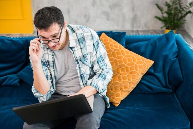 Intelligenter mann, der auf sofa sitzt und laptop betrachtet Kostenlose Fotos
