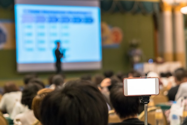 Intelligentes mobiltelefon, das live-streaming zu asiatischem sprecher mit beiläufigem anzug auf der bühne vor tut Premium Fotos