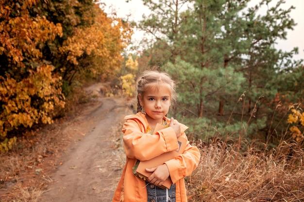 Intelligentes nettes kindermädchen, das ein buch mit trockenen gelben blättern hält Premium Fotos