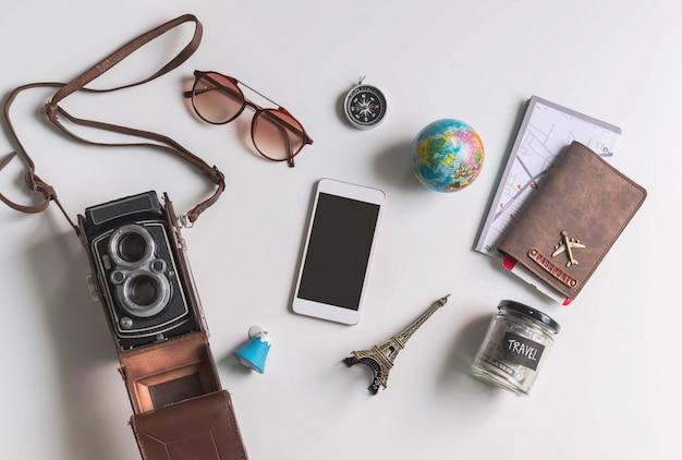 Intelligentes telefon des leeren bildschirms mit reisezubehör und -einzelteilen auf weißem hintergrund mit kopienraum Premium Fotos