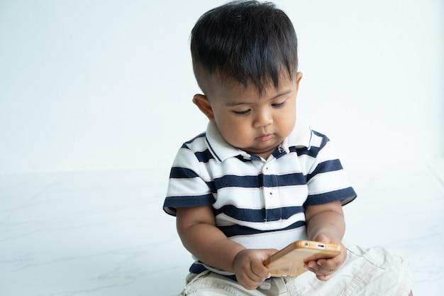 Intelligentes telefon des netten kleinen asiatischen babyspiels Premium Fotos