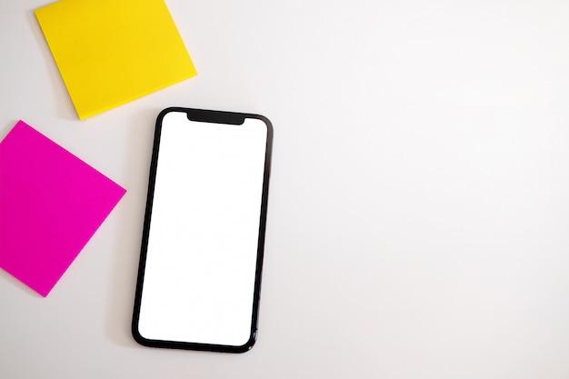 Intelligentes telefon mit weißem leerem leerem schirm auf weißer schreibtischtabelle. Premium Fotos