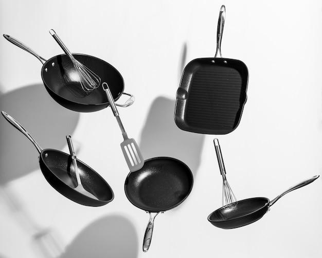 Interessante aufnahme von trendigen schwarzen küchenutensilien, die auf weißem hintergrund tanzen Kostenlose Fotos