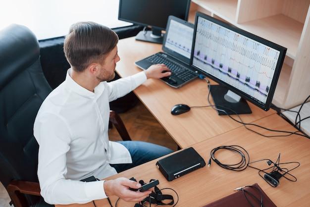 Interessante ergebnisse. der polygraph-prüfer arbeitet im büro mit der ausrüstung seines lügendetektors Kostenlose Fotos