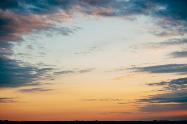 Interessanter landschaftssonnenunterganghimmel. blaue wolken weichen vor dem roten himmel auseinander. faszinierender moment. Premium Fotos