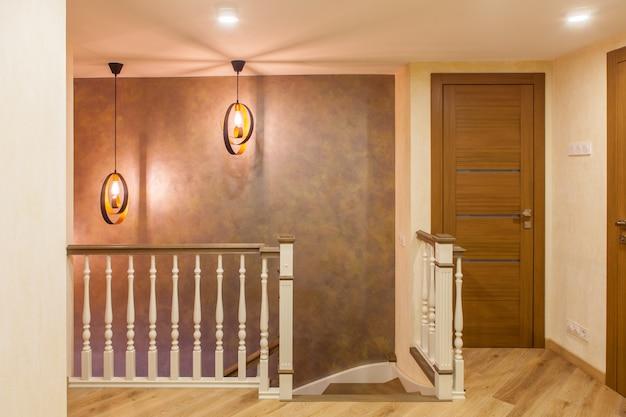 Interieur im klassischen stil in einem zweistöckigen apartment. weiße holztreppe in der halle im zweiten stock mit modernem blitz. Premium Fotos