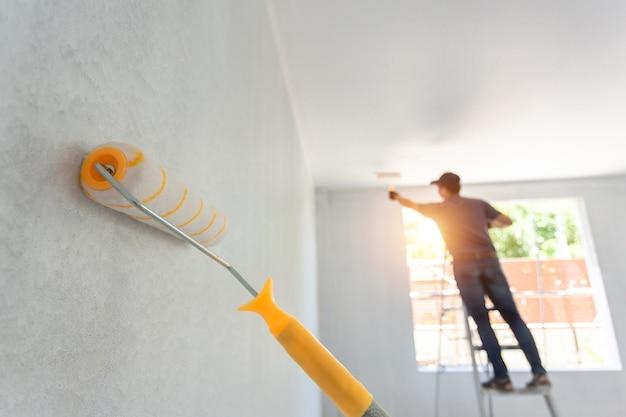 Interior painting roller und der arbeiter im hintergrund. home remodeling konzept. Premium Fotos