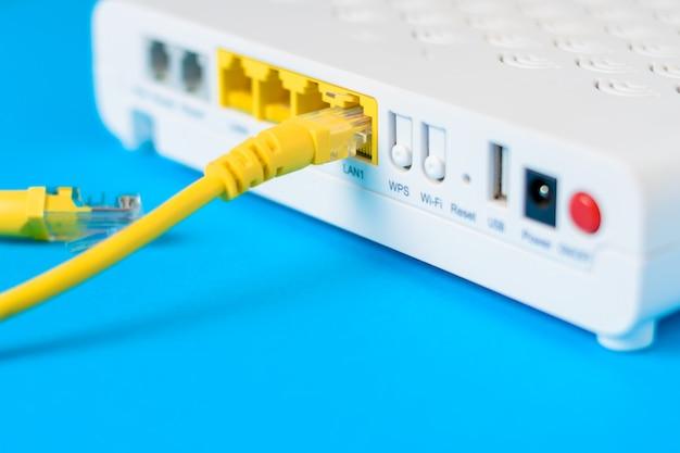 Internetmodemroutennabe mit einem kabel, das auf blauem hintergrund anschließt Premium Fotos