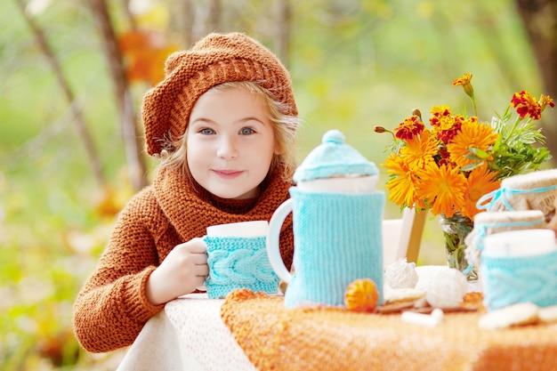 Irl, der teeparty draußen im herbstgarten hat. mädchen tee trinken. Premium Fotos