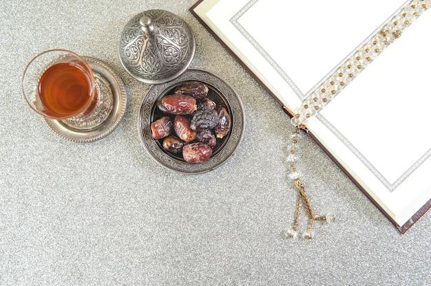 Islam kurma, ramadan, dattelpalme früchte und tee auf einem metalltablett gelegt Premium Fotos