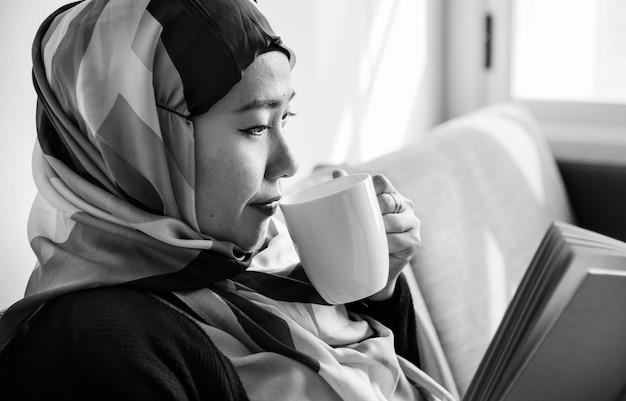 Islamische frau, die kaffee liest und trinkt Kostenlose Fotos