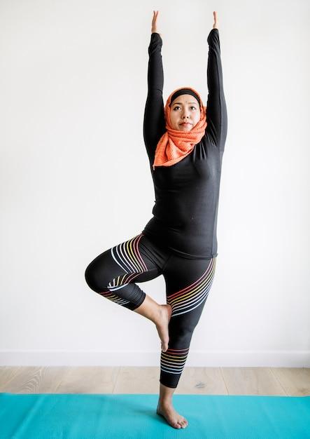 Islamische frau, die yoga im raum tut Kostenlose Fotos