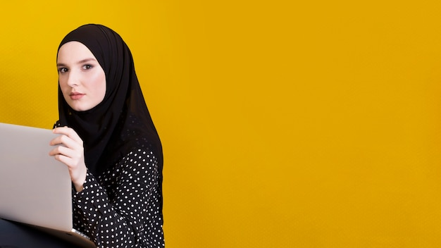 Islamische frau, welche die kamera hält laptop über hellem gelbem hintergrund betrachtet Kostenlose Fotos