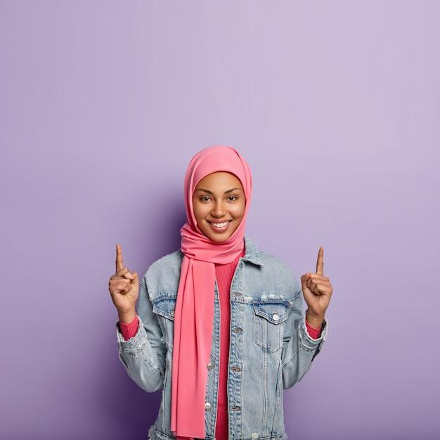 Islamisches modekonzept. frohes positives weibchen mit spezifischem aussehen und kleidung, punkte oben auf freiem raum, zeigt etwas nach oben, trägt modische jacke. mädchen im hijab wirbt für objekt Kostenlose Fotos