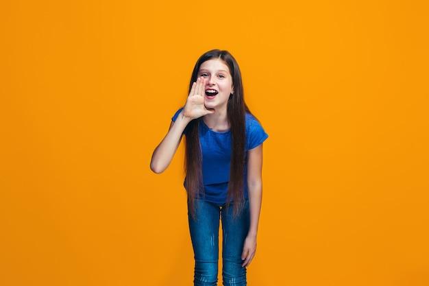 Isoliert auf gelbes junges lässiges jugendlich mädchen, das im studio schreit Kostenlose Fotos