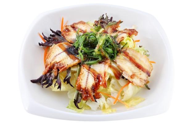 Isoliert auf weißer tiefer schüssel mit scheiben des geräucherten aals, liegend auf blättern des frischen salats, verziert mit seetang chuka. Premium Fotos
