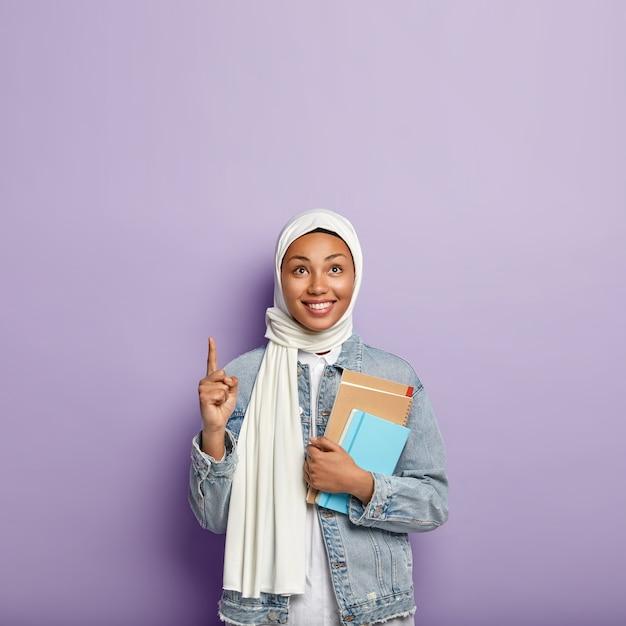 Isolierte aufnahme der fröhlichen religiösen frau bedeckt kopf mit schleier, trägt notizblock, zeigt oben mit dem zeigefinger, lächelt fröhlich, steht über lila wand, leerzeichen für beförderung. islamische mädchenstudien Kostenlose Fotos