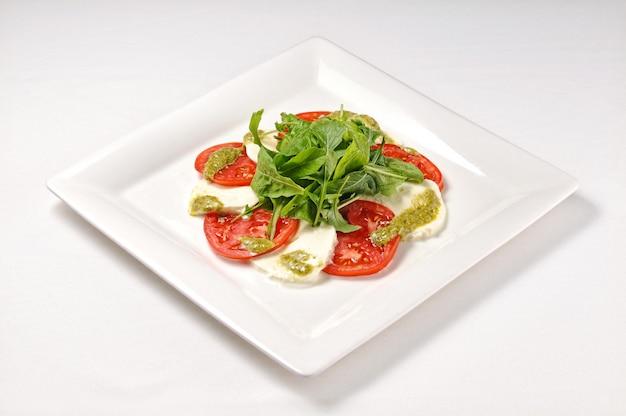 Isolierte aufnahme eines weißen tellers mit caprese-salat - perfekt für einen food-blog oder eine menüverwendung Kostenlose Fotos