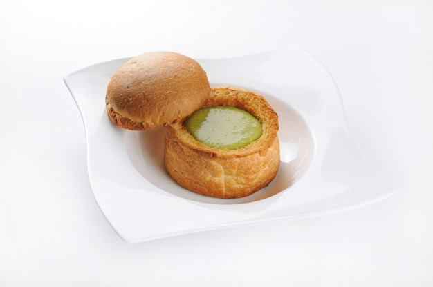 Isolierte aufnahme eines weißen tellers mit gebäck mit grüner soße - perfekt für lebensmittelblog oder menüverwendung Kostenlose Fotos