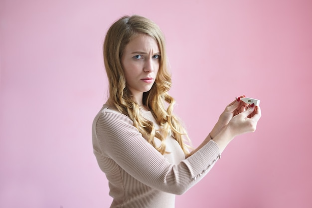 Isoliertes horizontales bild einer frustrierten verärgerten jungen europäischen dame mit blonder, gewellter frisur, die die stirn runzelt, sich besorgt und ängstlich fühlt, einen positiven schwangerschaftstest hat und sich über ihre entscheidung nicht sicher ist. Kostenlose Fotos