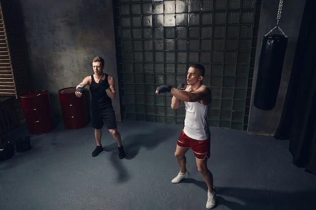 Isoliertes porträt in voller länge von zwei hübschen kaukasischen männern, die drinnen zusammen in stilvoller sportkleidung und in boxverbänden trainieren und hände ausstrecken, während sie schläge im modernen fitnessstudio meistern Kostenlose Fotos