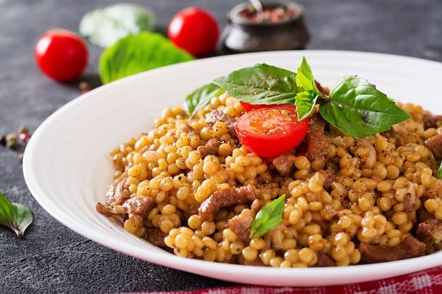 Israelischer couscous mit rindfleisch. Premium Fotos