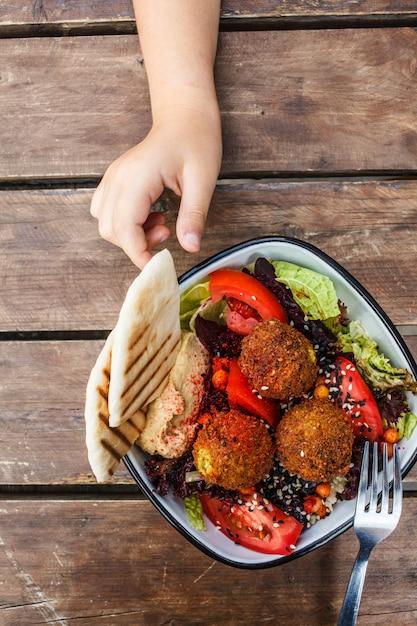 Israelisches straßenessen. falafel-salat mit hummus, rote-bete-wurzeln und gemüse in der schüssel auf holztisch, draufsicht. Premium Fotos