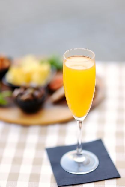 Italienische aperitifs / aperitifs: ein glas cocktail (sekt mit aperol) und eine vorspeisenplatte auf dem tisch Premium Fotos