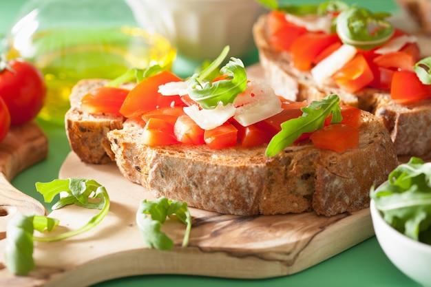 Italienische bruschetta mit tomaten-parmesan-rucola Premium Fotos