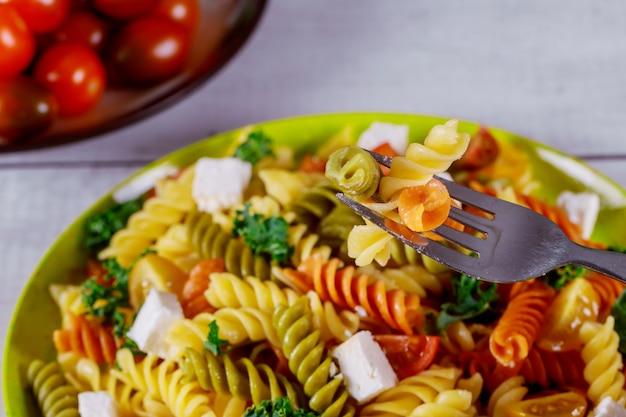 Italienische bunte nudelrotini mit kirschtomaten auf weißem hölzernem hintergrund. Premium Fotos