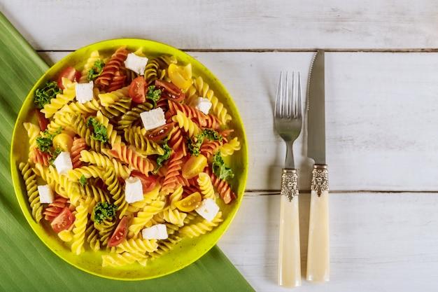 Italienische bunte nudelrotini mit kirschtomaten auf weißer holzoberfläche Premium Fotos