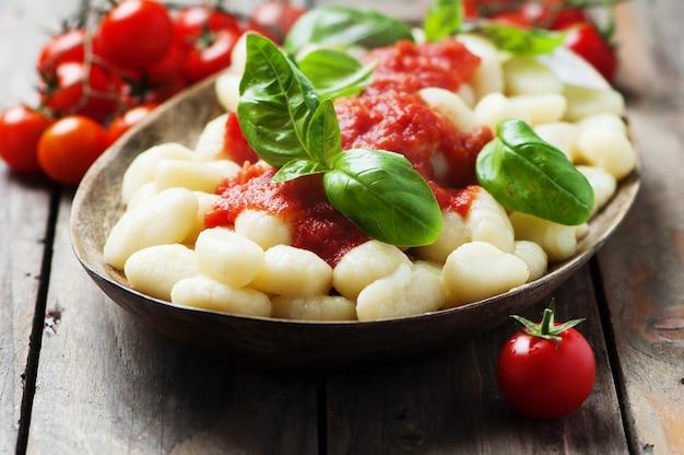 Italienische gnocchi mit tomaten und basilikum Premium Fotos