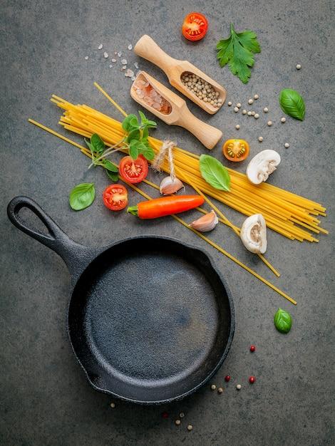 Italienische lebensmittel- und menükonzeptspaghettis mit bestandteilen auf dunkler tabelle. Premium Fotos