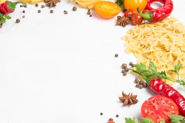 Italienische nudeln verschiedener arten mit gewürzen, paprika, eiern, gelben und roten tomaten auf einem weißen steinhintergrund. konzept, das italienische nudeln und soße kocht Premium Fotos