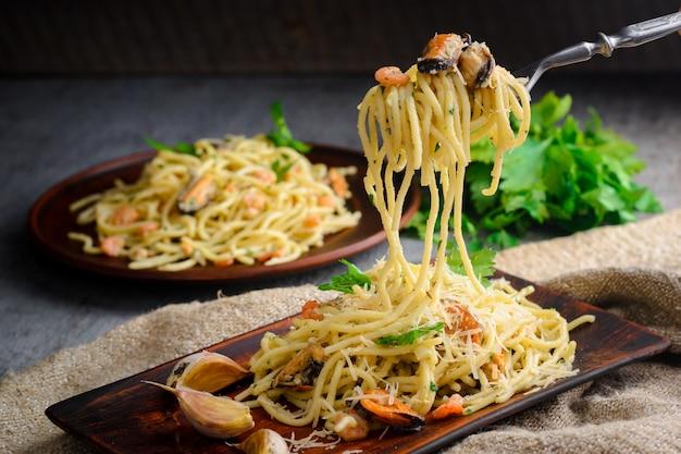 Italienische pasta in einer cremigen sauce mit meeresfrüchten, garnelen und muscheln auf einem teller Premium Fotos