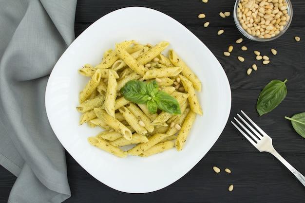 Italienische pasta mit pesto und pinienkernen in der weißen platte auf dem schwarzen holztisch Premium Fotos