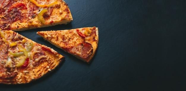 Italienische pizza auf einem schwarzen hintergrund mit draufsicht. platz für text Premium Fotos