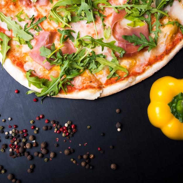 Italienische pizza; gelbe paprika und schwarzer pfeffer auf küchentheke Kostenlose Fotos