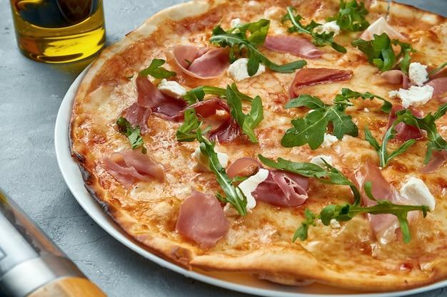 Italienische pizza mit jamon, rucola und frischkäse Premium Fotos