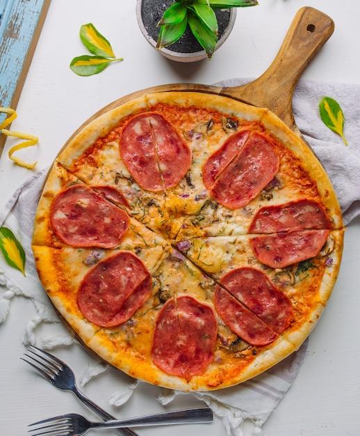 Italienische pizza mit salamiwürsten, dill, pilz, roter zwiebel, käse auf weißem hintergrund Kostenlose Fotos