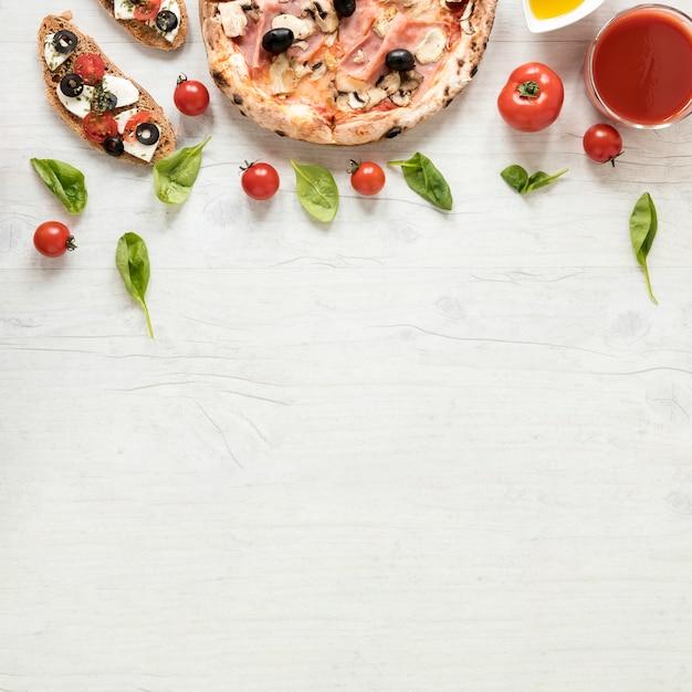 Italienische pizza und bruschetta mit bestandteil über hölzernem strukturiertem hintergrund Kostenlose Fotos