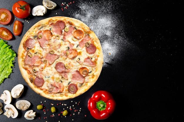 Italienische pizza und zutaten. pilze, tomaten, pfeffer, salz, kräuter und lebendig auf einem schwarzen betontisch. draufsicht Premium Fotos