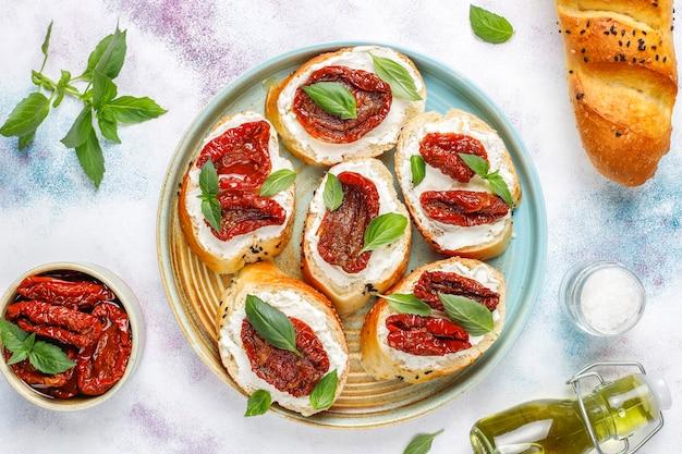 Italienische sandwiches - bruschetta mit käse, trockenen tomaten und basilikum. Kostenlose Fotos