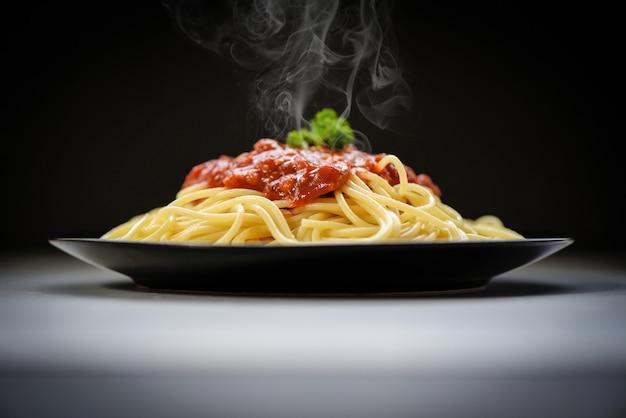 Italienische spaghetti-nudeln, serviert auf schwarzem teller mit tomatensauce und petersilie im italienischen speise- und menükonzept des restaurants. spaghetti bolognese auf schwarz Premium Fotos