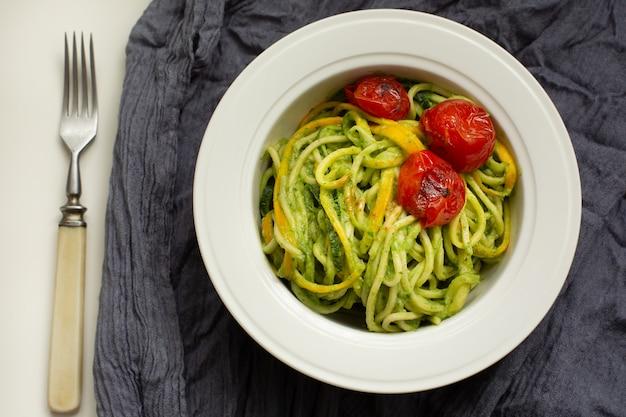 Italienische teigwaren mit zucchininudeln mit avocadosoßenpesto und gebratener tomate in der weißen platte. graues textil der draufsicht. gesundes essen . Premium Fotos