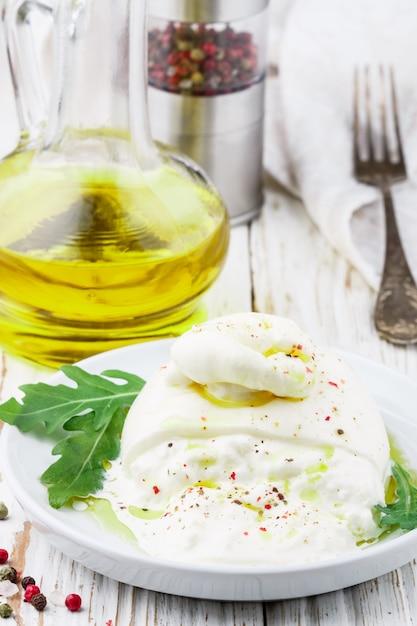 Italienischer burrata-frischkäse mit olivenöl, frischem rucola, rosa, grünem und schwarzem pfeffer Premium Fotos