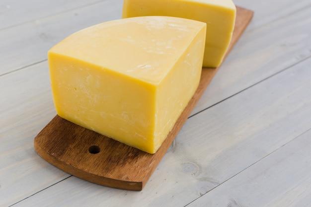 Italienischer käse auf hölzernem hackendem brett über dem schreibtisch Kostenlose Fotos